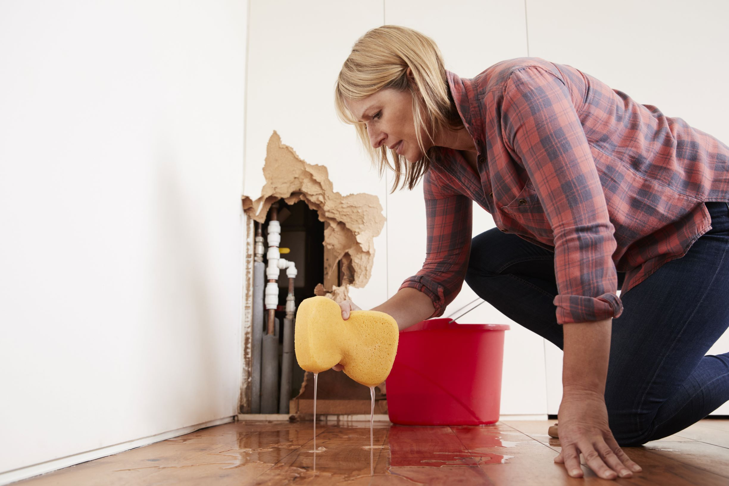 Woman cleaning up after a water pipe bursts.
